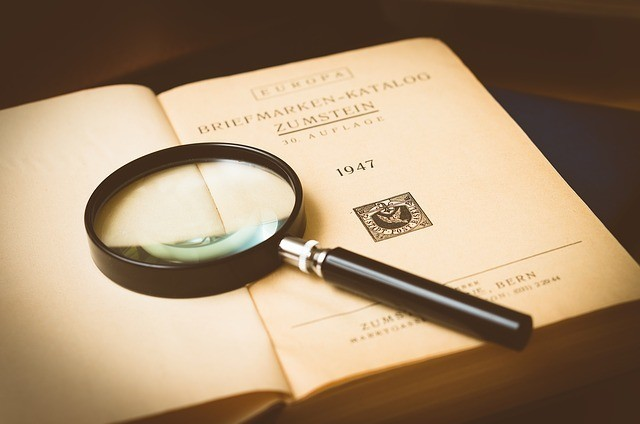 A magnifying glass lying on a book. This is to represent trying to find out just exactly what A scam is.