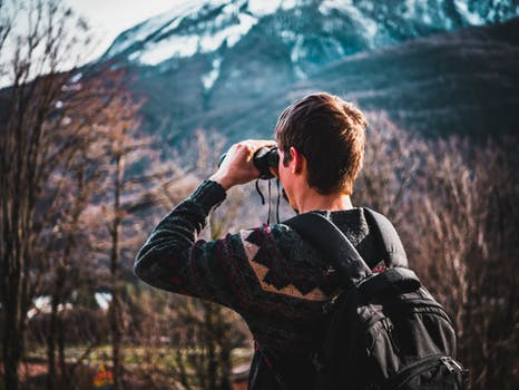 Image of a man looking through binoculars, and exploring the world around him.